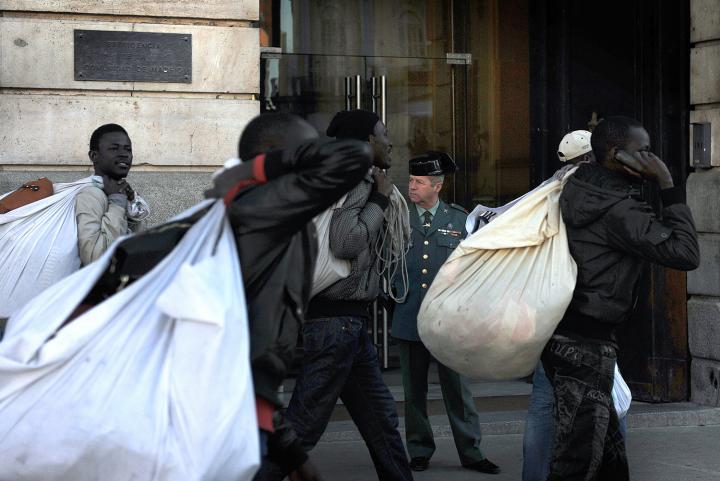 Fotografía de Fernando Sánchez para Nthephoto. Varios manteros pasan frente a un guardia civil en la sede de la comunidad de Madrid.