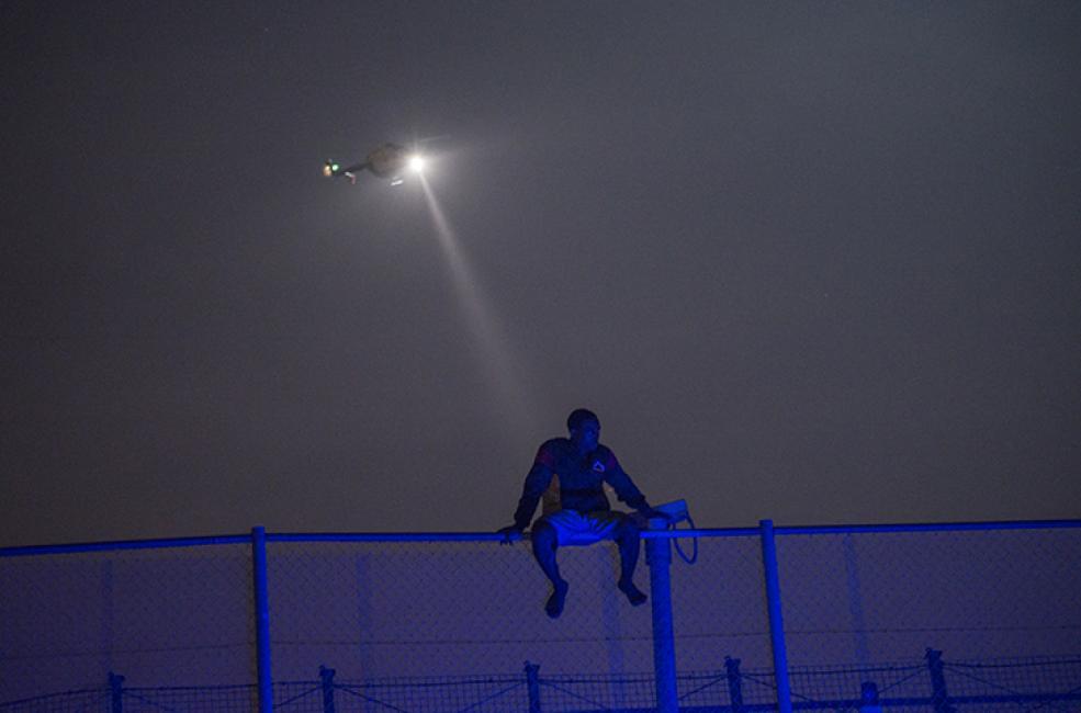 Fotografía de Jesús Blasco de Avellaneda para Nthephoto. El helicóptero de la Guardia Civil alumbra a un joven subsahariano encaramado en lo alto de la valla fronteriza entre Melilla y Marruecos.