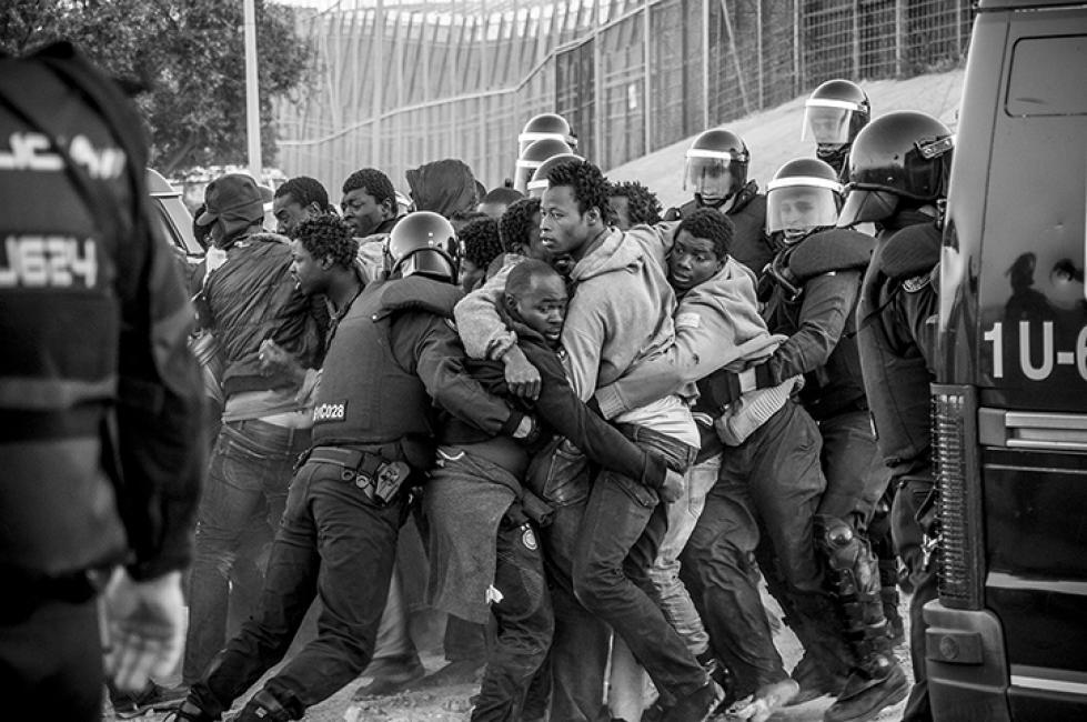 Fotografía de Jesús Blasco de Avellaneda para Nthephoto. Un grupo de inmigrantes subsaharianos acaba de saltar la triple valla de cuchillas que separa la provincia marroquí de Nador de la ciudad española de Melilla e intenta romper el cordón policial para correr hacia el centro de acogida de inmigrantes y no ser devueltos a Marruecos