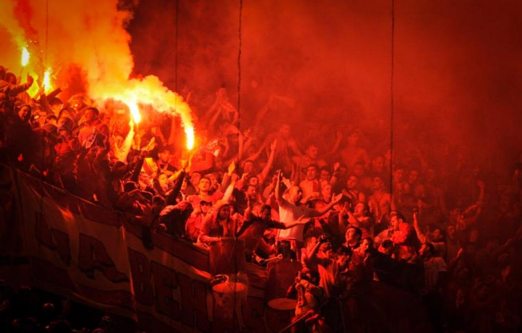 Fotografía de Pablo González para Nthephoto. La hinchada del Galatasaray encienden bengalas durante el un partido de Champions League frente al Real Madrid en el estadio Santiago Bernabeu