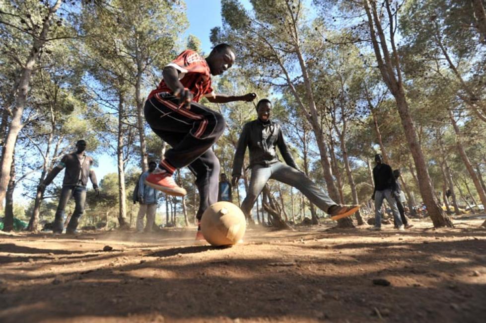Fotografía de Pablo González-Cebrián para Nthephoto. Inmigrantes jugando al fútbol mientras esperan en el Monte Gurugú la posibilidad de saltar la valla de Melilla.