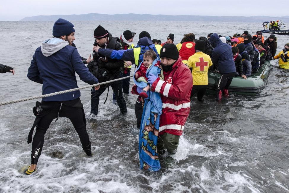 Fotografía de Iker Pastor para Nthephoto. Un voluntario de la Cruz Roja griega, lleva en sus brazos a un bebe completamente calado en la costa griega de Skala Sikamineas, en el mar Egeo, Grecia.
