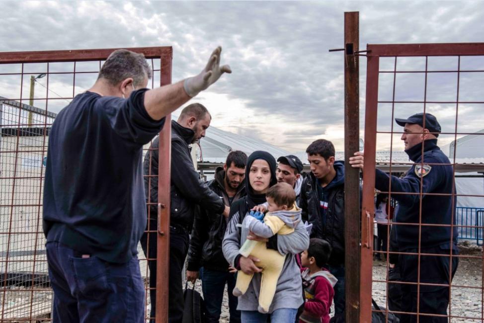 Fotografía de Iker Pastor para Nthephoto. Un agente de fronteras macedonio hace señas a una madre con su bebé para que suban a bordo de un tren a Serbia