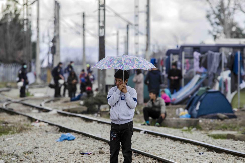 Fotografía de Iker Pastor para Nthephoto. Un niño sostiene un paraguas en las vias de tren del campo de refugiados de Idomeni