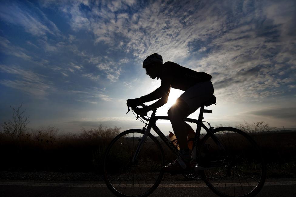 Fotografía de Juan José Úbeda Díaz de Argandoña para Nthephoto. Desafío Doñana de Triatlón 2011. Un triatleta se escapa del grupo para liderar el tramo ciclista con el amanecer en los campos de Cádiz de fondo.