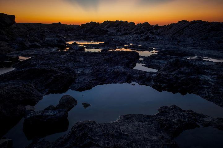 Fotografía de Hugo Rodriguez para Nthephoto. Cap Favaritx, Menorca. Era casi de noche pero aún quedaba algo de luz en el cielo anaranjado. Tomé con varias exposiciones para mostrar el detalle en toda la escena incluso bajo el contraste extremo de la situación.