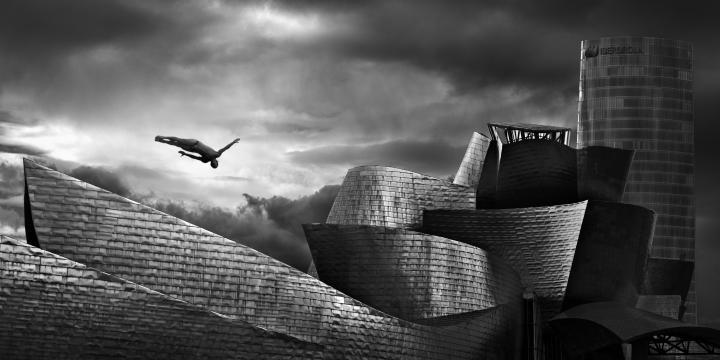 Fotografía de ENRIQUE  MORENO ESQUIBEL para Nthephoto. 1º Premio Nikon. SALTO del Red Bull Cliift Diving.en la fotografia se ve el museo Guggenheim Bilbao y la Torre Iberdrola.